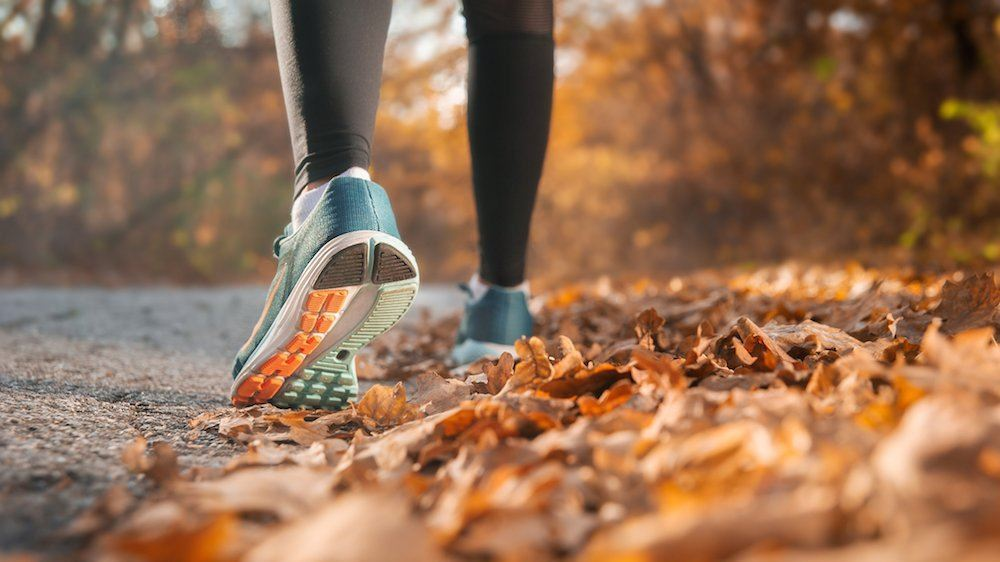 Photo of person&#39s lower leg and shoe as they are running through fall leaves.