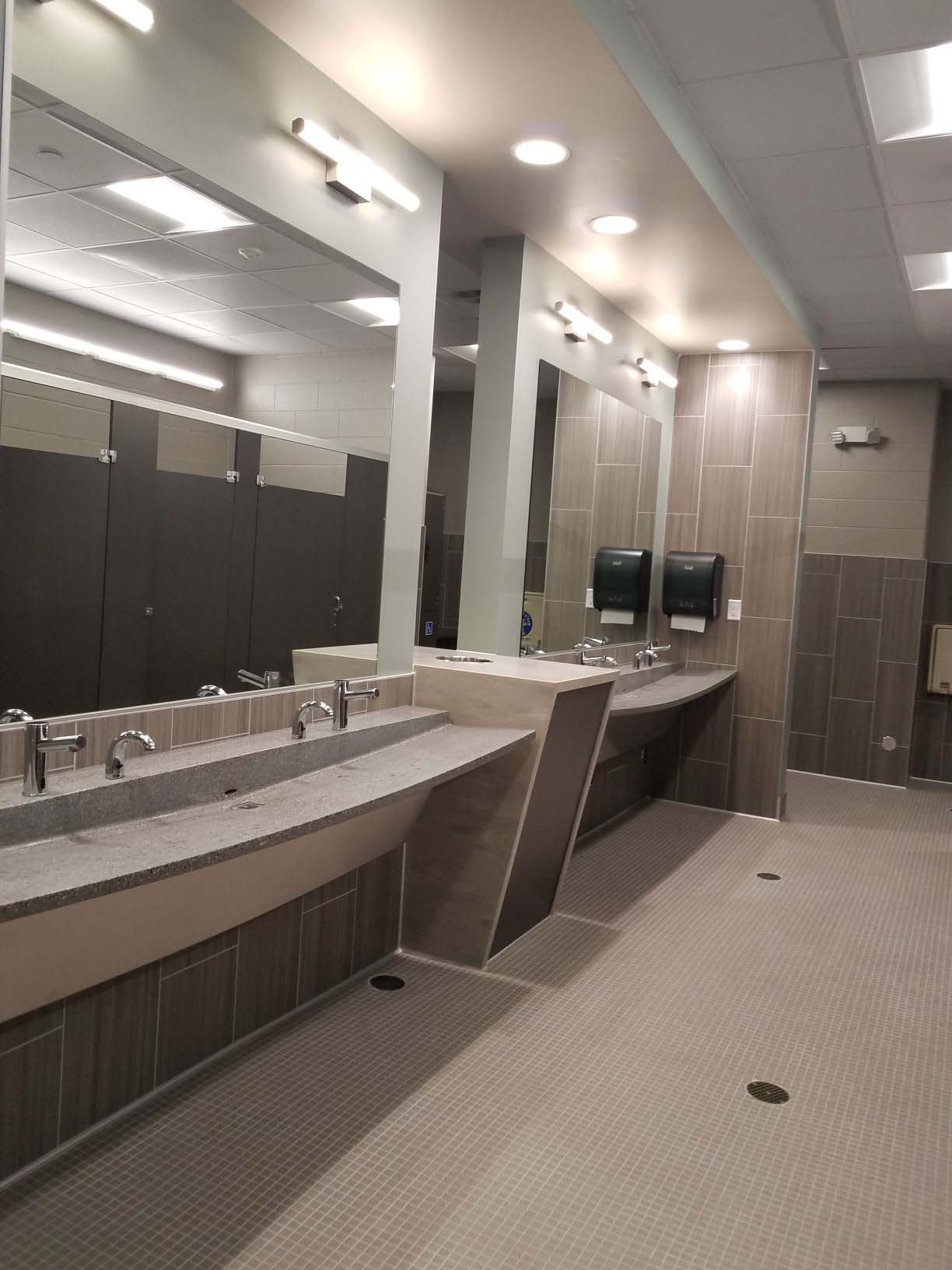 Modern gray/brown bathroom doors, off white tile,  counter tops and floors, mirrors, hanging lights