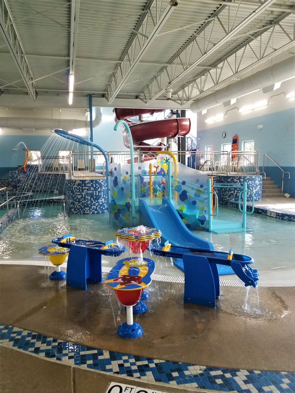 Play feature in actvity pool with fountains and small slide.