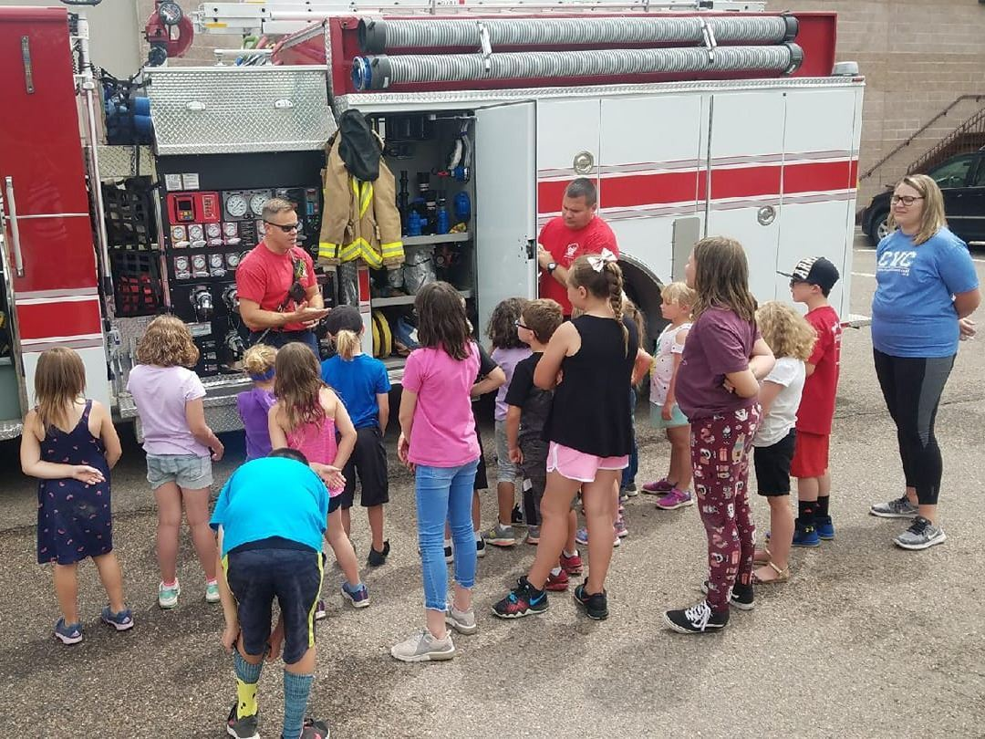 Summer camp kids looking at a fire truck with a fireman talking.