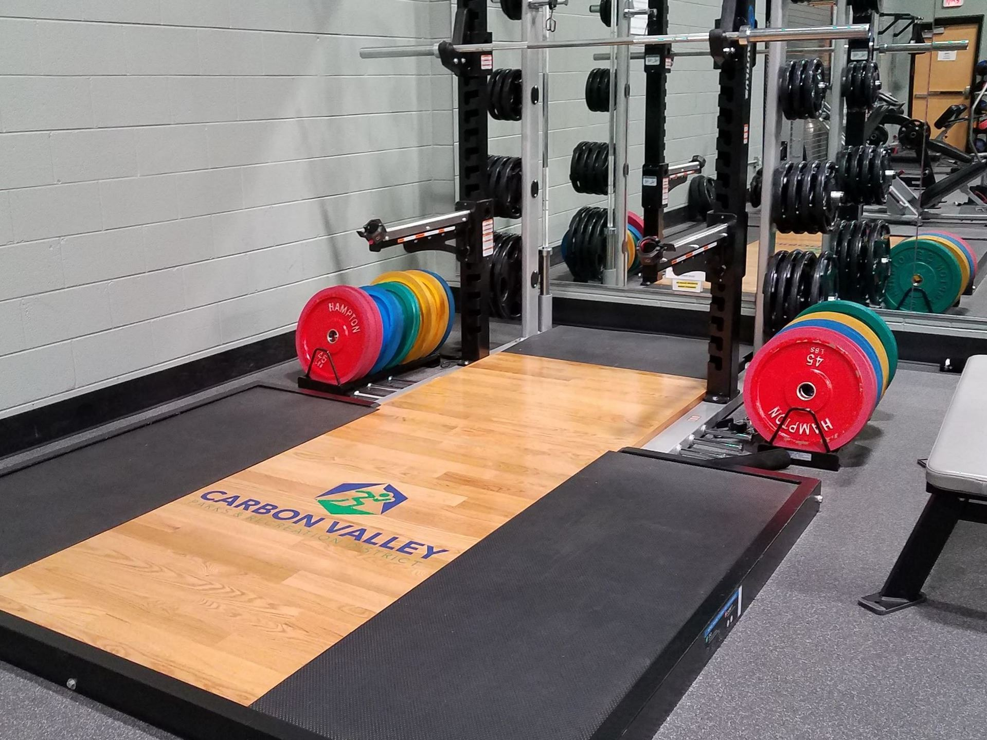 Wood floor platform with CVPRD logo painted on it with weight rack next to it.