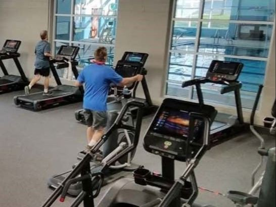 Cardio room with people on treadmill and stair climber machines.