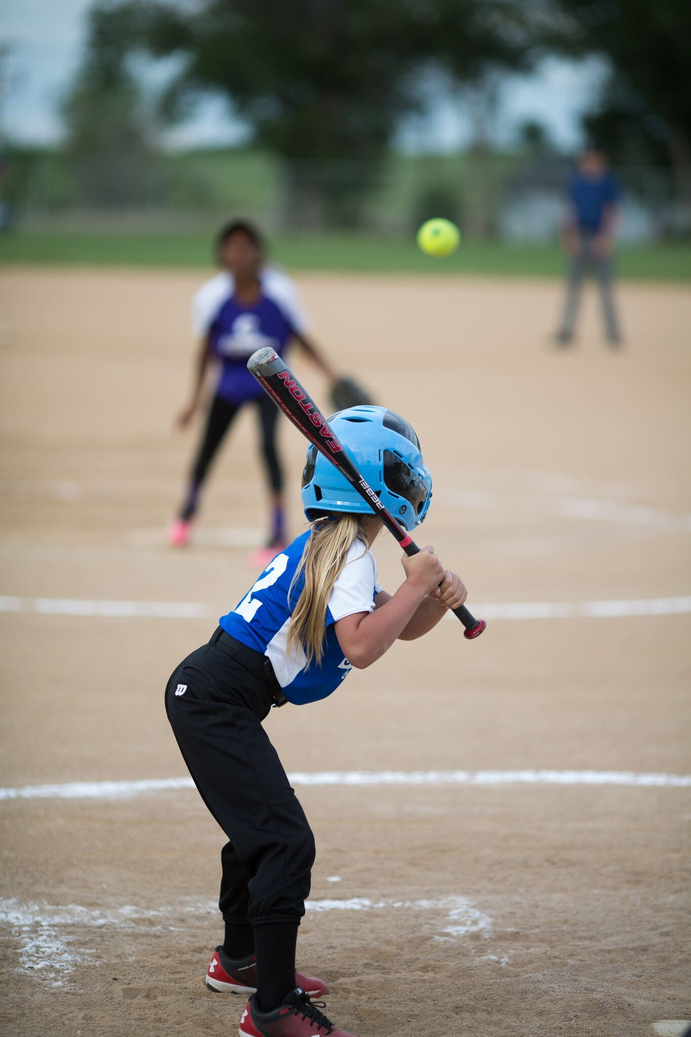 Young girl getting ready to swing the bat while receiving a pitch.