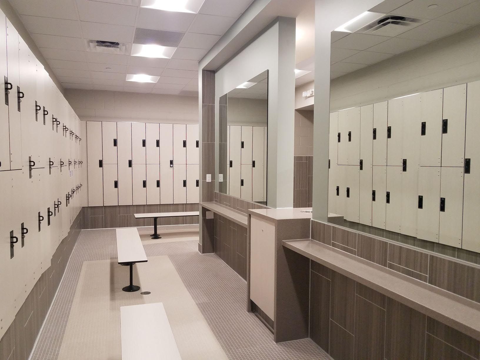 Modern off white lockers, off white floor tile and counter, mirrors, brown benches.