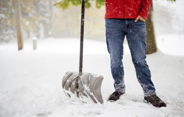 Man standing in snow holding snow shovel.