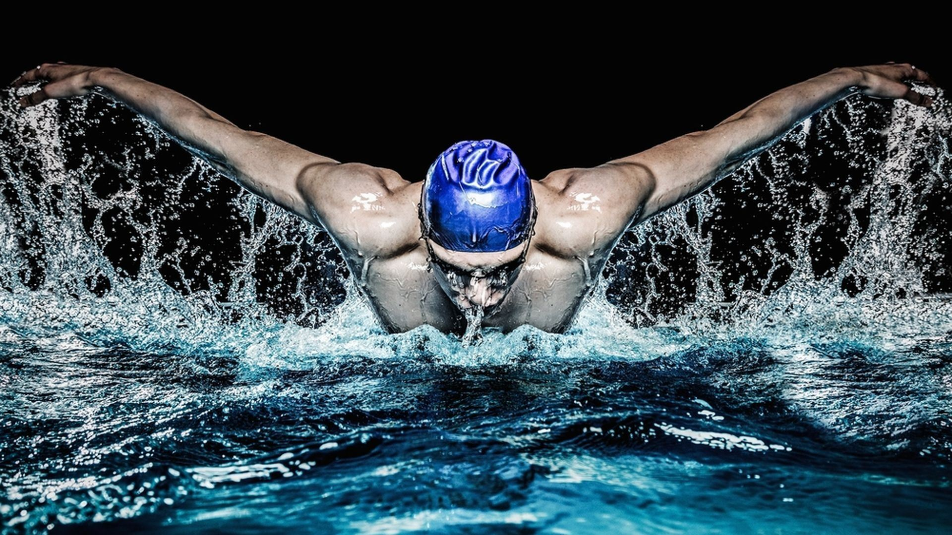 Man swimming butterfly stroke with water splashing off body.