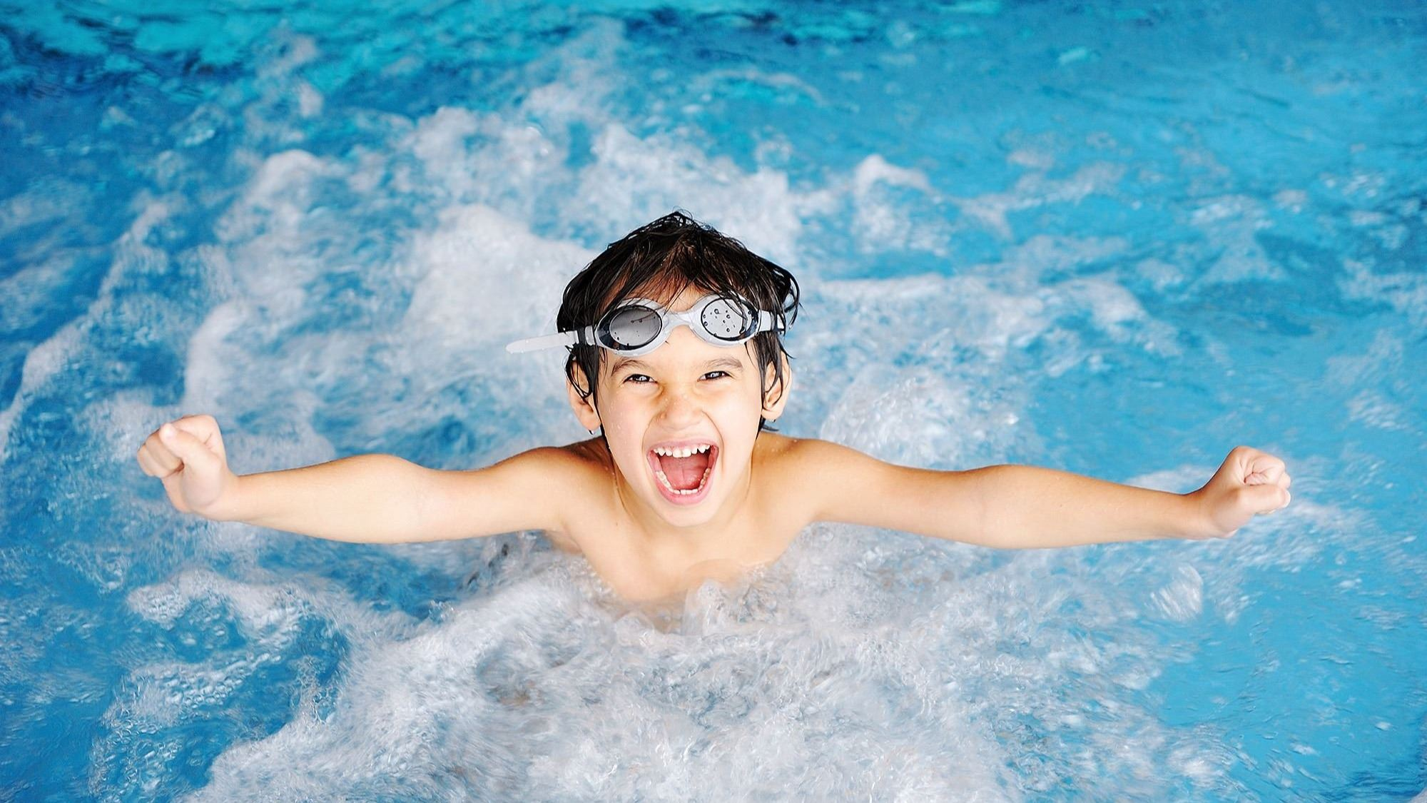 Boy splashing in pool with goggles on his head.